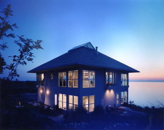 Lakefont residence on Lake Erie · Bratenahl · Contemporary design at dusk showing Breezy Bluff Condominium Development